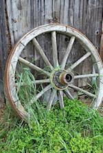A Vintage Old Wooden Wagon Wheel Leaning Against a Wall Journal