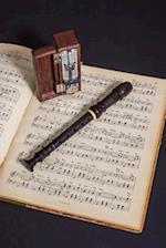 A Wooden Recorder, Metronome, and Sheet Music Journal
